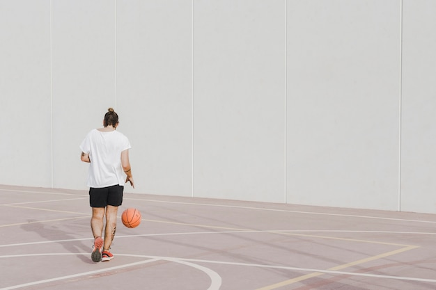 Vista posterior de un joven praticing baloncesto