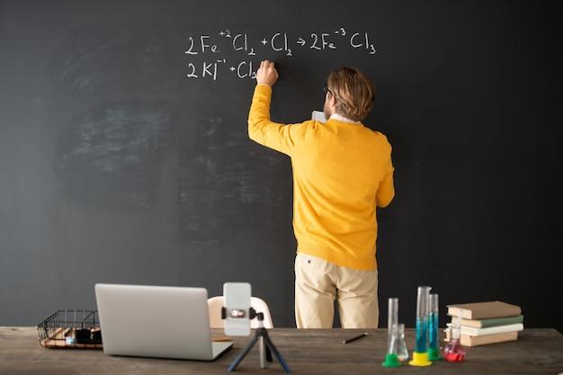 Vista posterior del joven profesor de química escribiendo la fórmula química en la pizarra con computadora portátil, libros, teléfonos inteligentes y tubos detrás