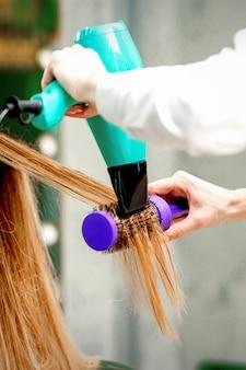 Vista posterior de la joven recibiendo secar el cabello con un secador de pelo y un cepillo para el cabello en una peluquería