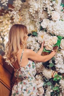 Vista posterior de una joven rubia arreglando las flores blancas