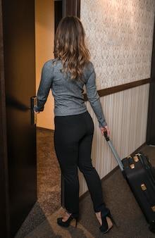 Vista posterior de una joven rubia con una maleta entrando en la habitación del hotel