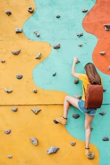 Vista posterior joven viajero muro de escalada