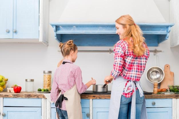 Vista posterior de la madre y su hija cocinando comida en la cocina.