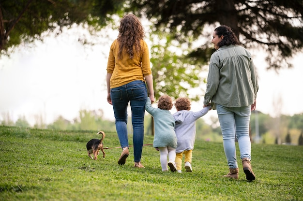 Vista posterior de madres lgbt afuera en el parque con sus hijos y su perro.