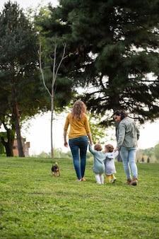 Vista posterior de madres lgbt afuera en el parque con sus hijos.