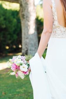 Vista posterior de la mano de la novia con un hermoso ramo de flores