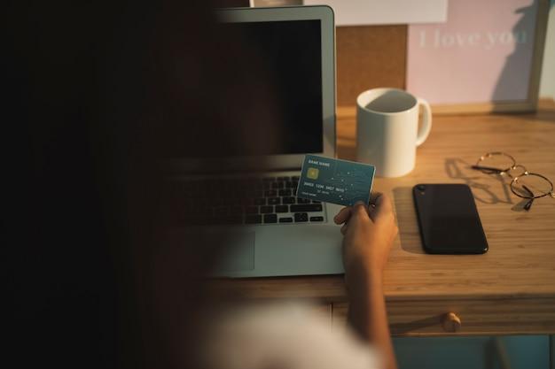 Vista posterior mano sosteniendo una tarjeta de crédito