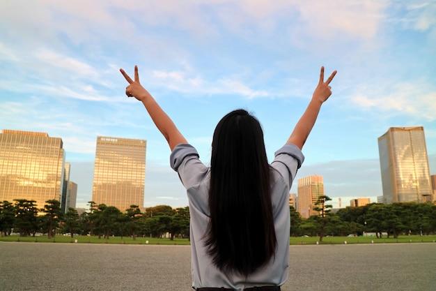 Vista posterior de las manos asiáticas del aumento de la mujer con el cielo azul claro, las nubes blancas y el edificio.