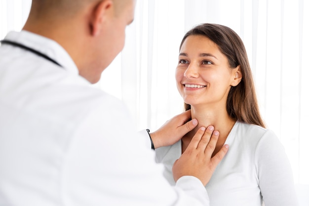 Vista posterior médico examinando el cuello de la mujer