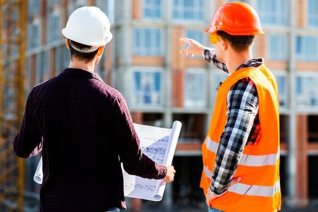 Vista posterior a medio tiro del ingeniero y arquitecto que supervisa la construcción.