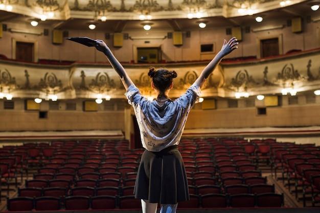 Vista posterior de un mimo femenino que levanta sus brazos