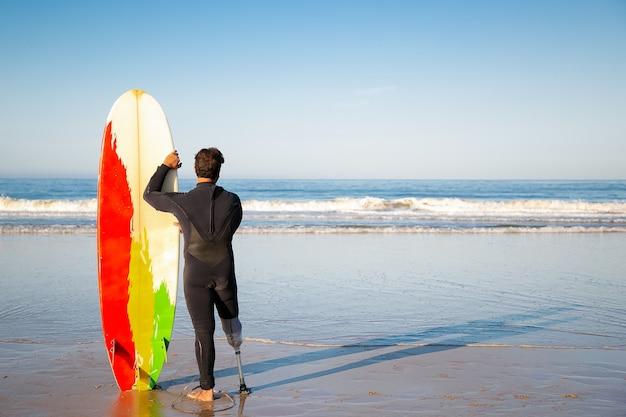 Vista posterior de la morena surfista de pie con tabla de surf en la playa