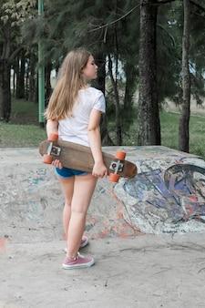 Vista posterior de la muchacha moderna que sostiene el monopatín que se coloca en parque