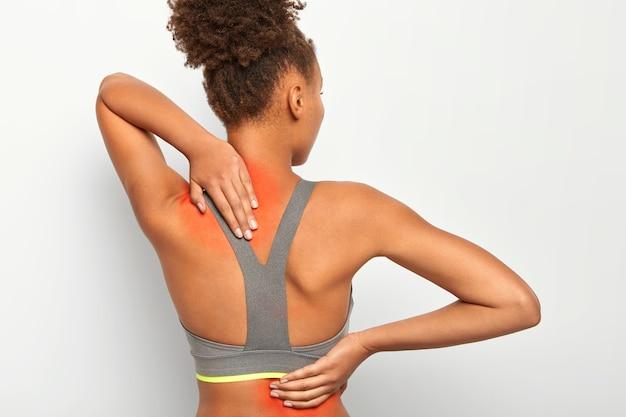 Vista posterior de la mujer afro toca la espalda y el cuello, muestra zonas inflamadas, posa contra la pared blanca