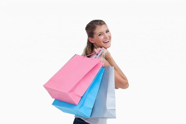 Vista posterior de una mujer alegre sosteniendo bolsas de compras