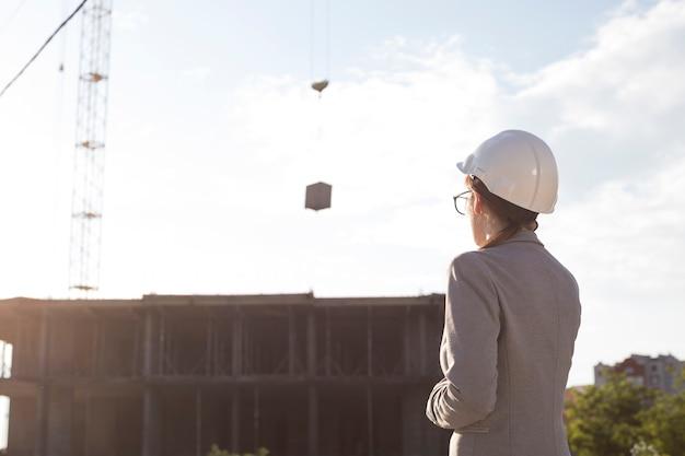 Vista posterior de la mujer arquitecto vistiendo sombrero hart mirando el sitio de construcción