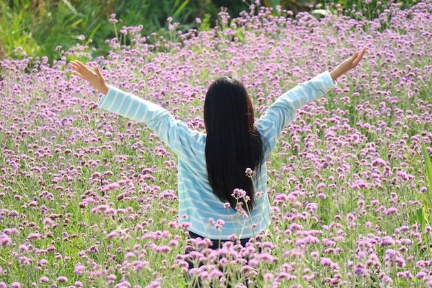 Vista posterior de la mujer asiática de pelo largo levantar las manos con un pequeño campo de flores moradas