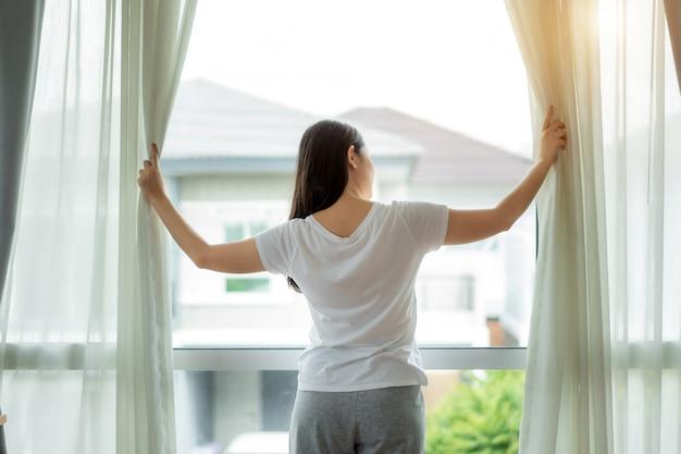Vista posterior de la mujer asiática que se despierta en su cama completamente descansada abriendo las cortinas de la ventana
