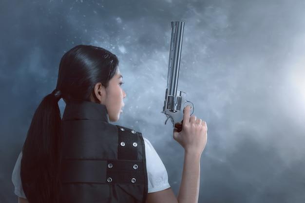 Vista posterior de mujer asiática con uniforme de policía sosteniendo armas