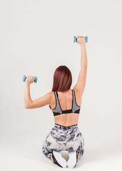 Vista posterior de la mujer en athleisure haciendo ejercicio con pesas