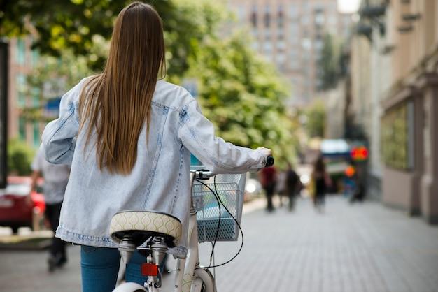 Vista posterior de una mujer caminando al lado de una bicicleta.