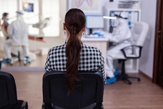 Vista posterior de la mujer en el consultorio del dentista esperando una consulta sentada en sillas en la sala de espera, asistente en traje de ppe llenando papeleo en la computadora, médico de dentista que consulta al paciente