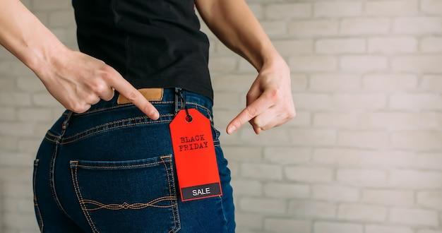 Vista posterior de una mujer delgada colillas en jeans. concepto de compra, descuentos de temporada.