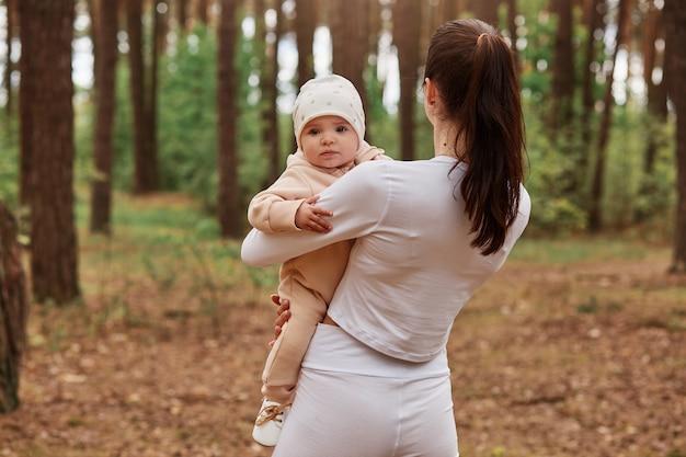 Vista posterior de la mujer delgada de pie en el bosque entre árboles y sosteniendo al bebé en las manos, niño mirando al frente