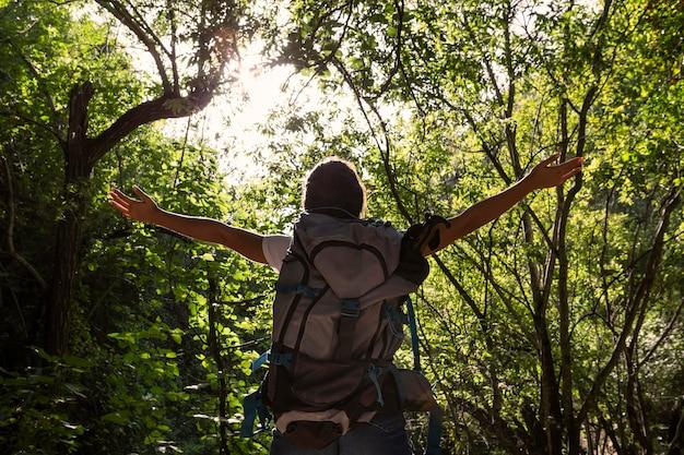 Vista posterior de la mujer despreocupada en la naturaleza con mochila