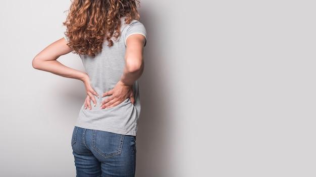 Vista posterior de la mujer con dolor de espalda contra el fondo gris