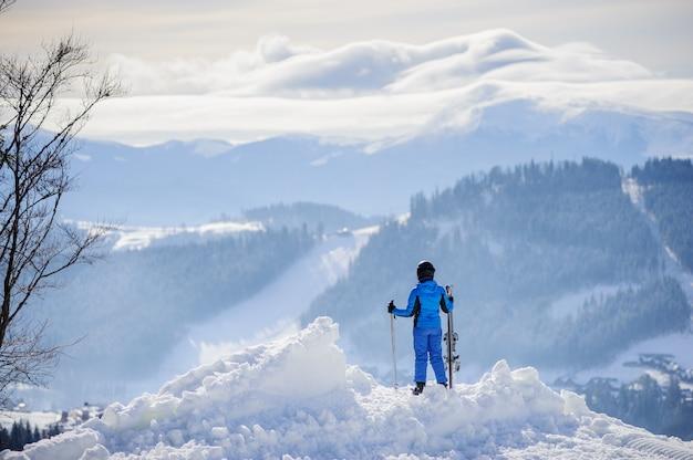 Vista posterior de la mujer esquiador de pie en la cima de la montaña y disfrutando de la vista en las hermosas montañas de invierno en un día soleado