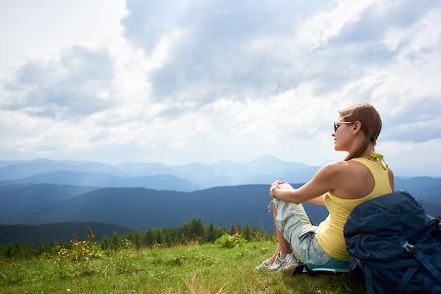 Vista posterior de la mujer feliz mochilero sentado y descansando en la colina cubierta de hierba con mochila