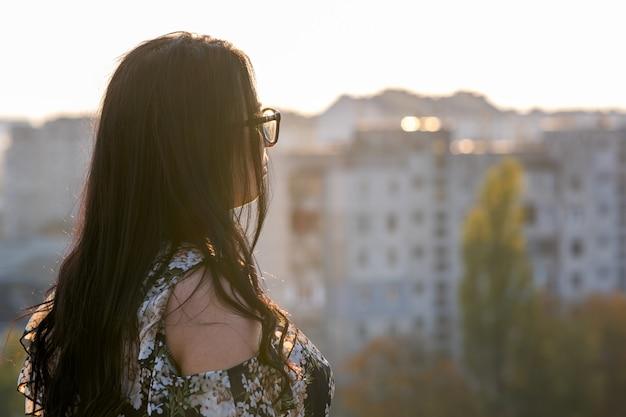 Vista posterior de una mujer con gafas mirando el paisaje de la ciudad.
