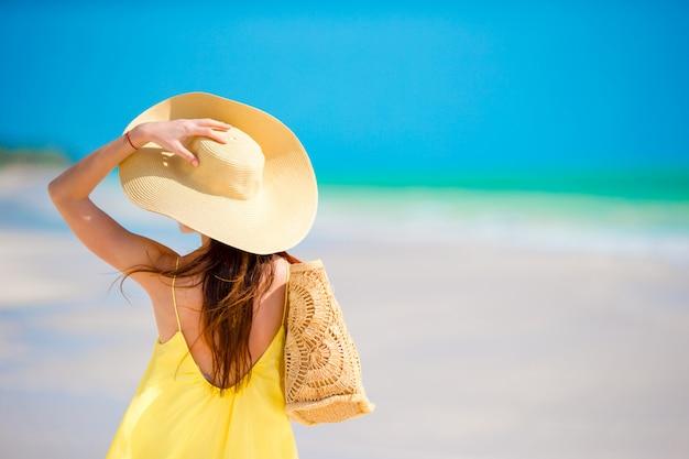 Vista posterior de la mujer en gran sombrero durante vacaciones en la playa tropical