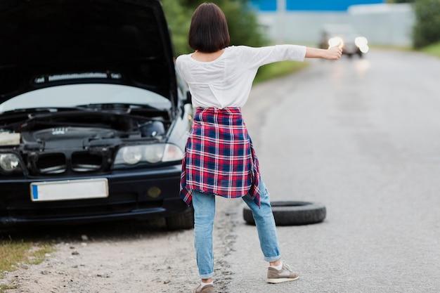 Vista posterior de una mujer haciendo autostop