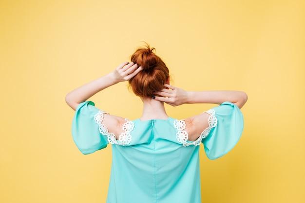 Vista posterior de la mujer de jengibre en vestido posando