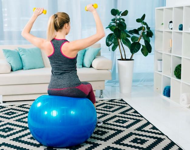 Vista posterior de la mujer joven de la aptitud que se sienta en la bola azul de los pilates que ejercita con pesas de gimnasia amarillas