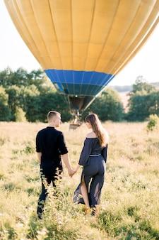 Vista posterior de una mujer joven feliz y un hombre en el campo de verano, listo para hacer un viaje en globo, de pie frente al globo aerostático tomados de la mano