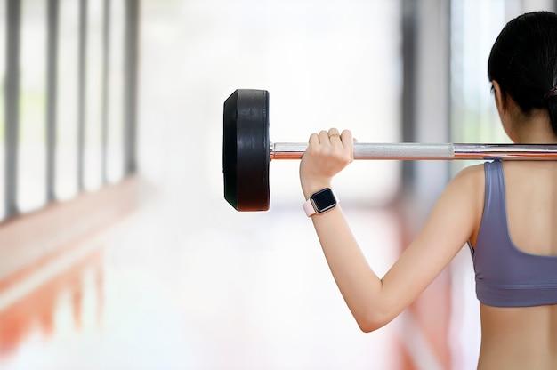 Vista posterior de la mujer joven en forma que lleva reloj inteligente y levantando pesas