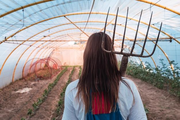 Vista posterior de una mujer joven con una herramienta de rastrillado de césped