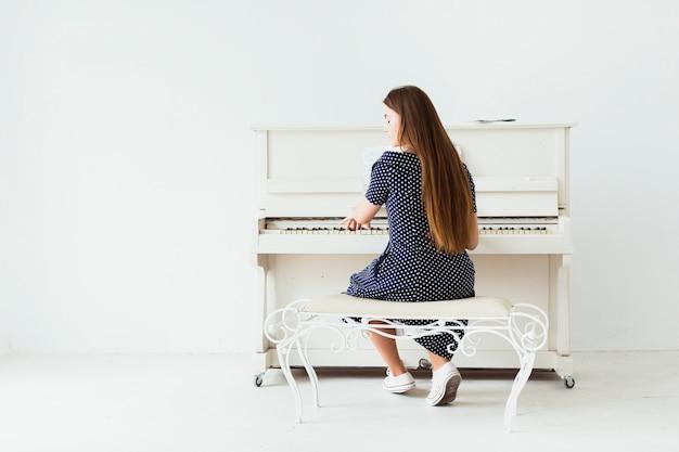 Vista posterior de una mujer joven con el pelo largo tocando el piano contra una pared blanca