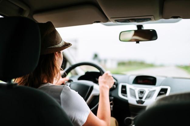 Vista posterior de la mujer joven que conduce un coche.
