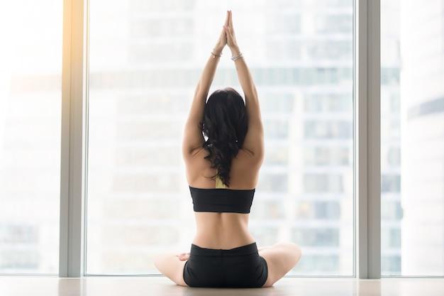 Vista posterior de la mujer joven que se sienta en la actitud de ardha padmasana