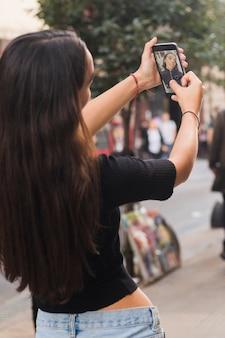 Vista posterior de una mujer joven que toma selfie en el teléfono móvil en la calle