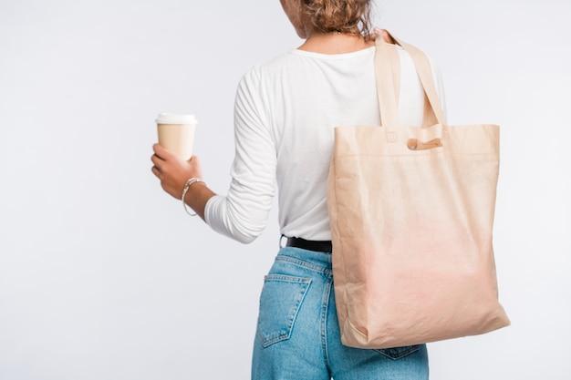 Vista posterior de la mujer joven en ropa casual con un vaso de café en la mano y un bolso de mano sobre el hombro