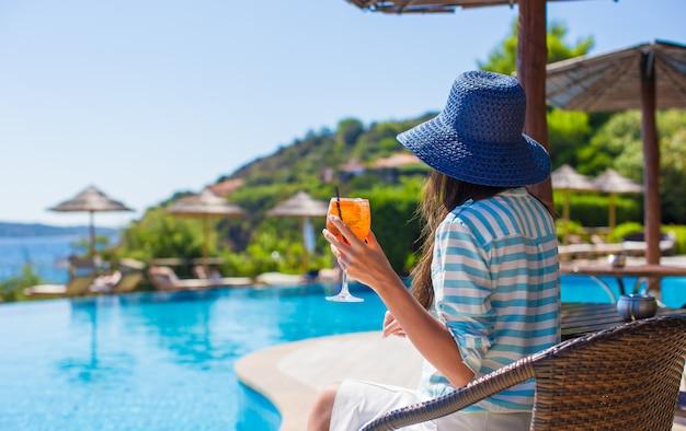 Vista posterior de una mujer joven sentada en un café tropical cerca de la piscina
