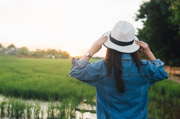 Vista posterior de la mujer joven con sombrero. muchacha que goza en la naturaleza hermosa con puesta del sol.