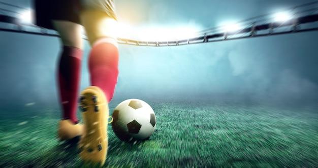 Vista posterior de la mujer del jugador de fútbol pateando la pelota en el campo de fútbol