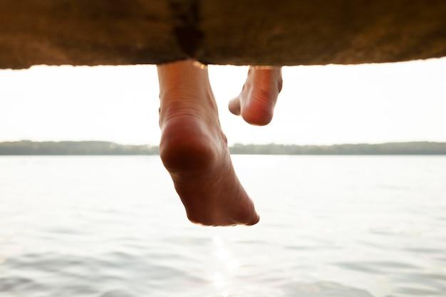 Vista posterior de la mujer jugando con los pies y el agua del lago