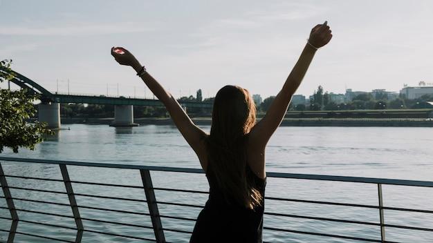 Vista posterior de una mujer levantando sus brazos frente al río